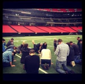 The PCC leadership team praying on the Georgia Dome field in preparation for Passion 2013. Courtesy of Instagram.